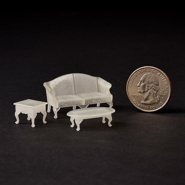Miniature living room set 3D printed in off-white Fine Detail Plastic next to US penny for size reference. The upright penny is about the same size as the set of furniture.